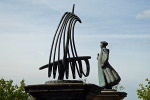 Willibrordus en het scheepje waarmee hij uit Engeland was overgestoken. Sculpturen op de ingangspoort van het Groene Kerkje.